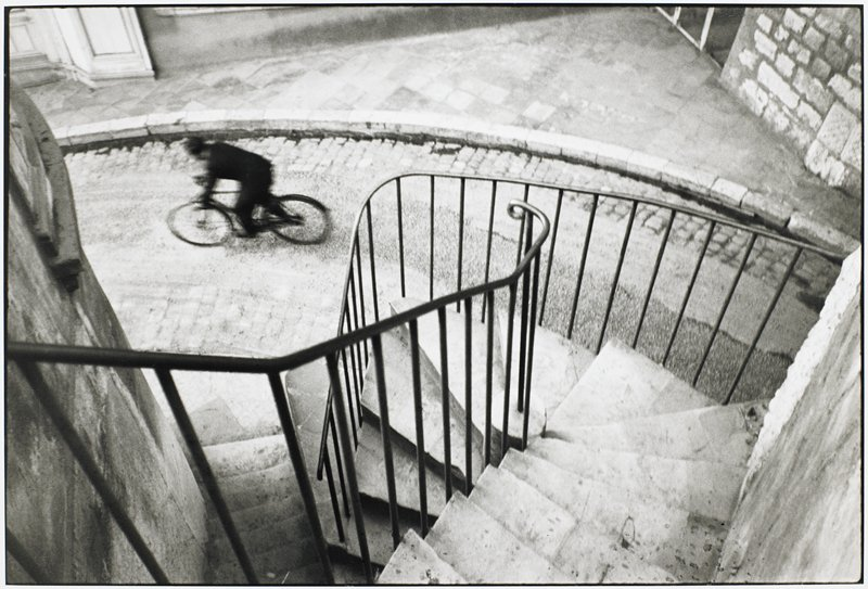 man on bicycle viewed from top of stairway; see L2005.262.312, which is the same image in larger size;