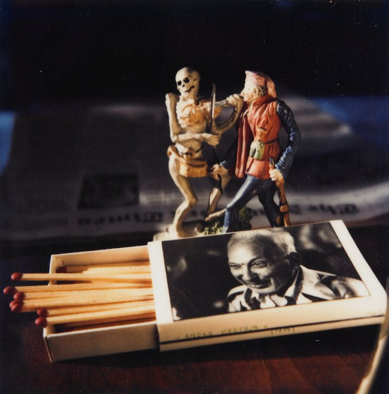 two small figurines of skeleton playing a violin and a man in red and blue behind an open matchbox with a photo of a smiling man on cover