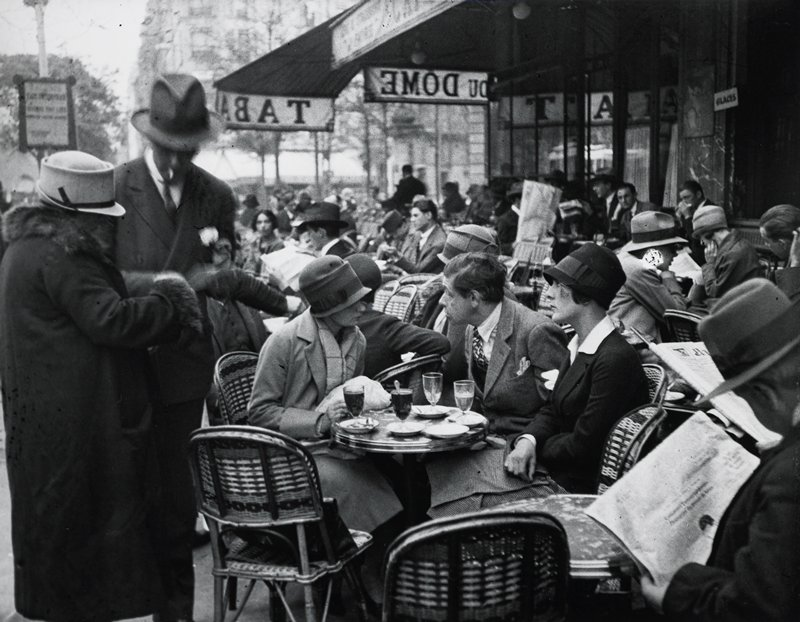 sidewalk cafe with many people seated at small tables; man and two women at table in foreground, with a standing man wearing a fedora and a woman wearing a fur-trimmed coat at left