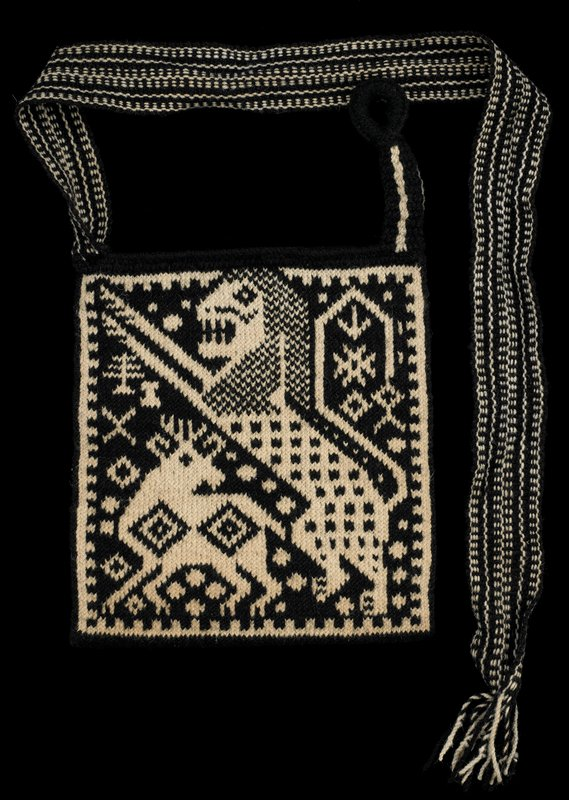 brown and off-white; one side decorated with flying bird; opposite side decorated with a lion and a deer; fringed strap fits though loop at other side of bag