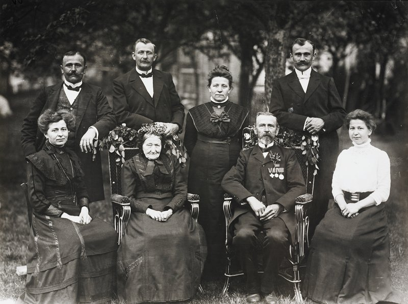 elderly man and woman seated in armchairs with branches on backs; woman in black seated to proper right of elderly woman; woman in white blouse and black skirt seated to proper left of elderly man; three men with moustaches and one woman stand in back of seated people