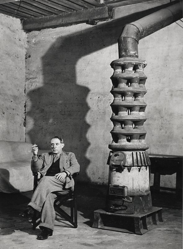seated man smoking cigarette; large stove with six-tiered openings between firebox and chimney