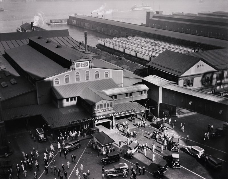 "waterfront scene; ferry terminal building with many people entering and leaving; building labeled ""Pier 16"" adjacent"