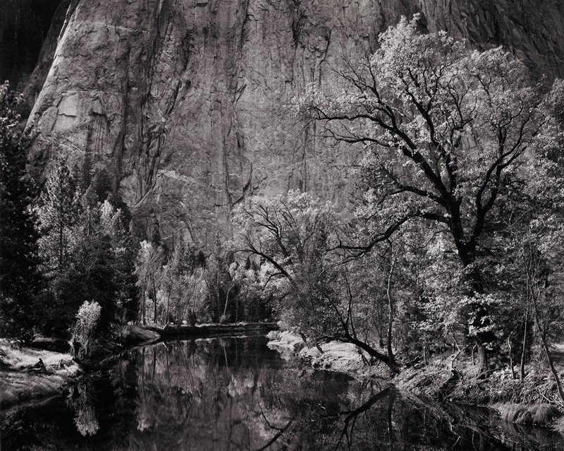 huge rock formation with river in foreground; trees along river bank; all reflected in river