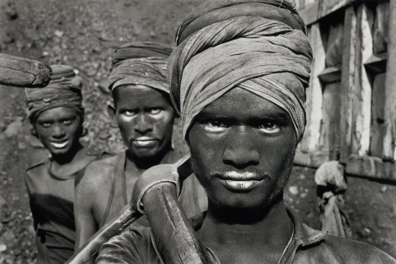 head and shoulders image of three dusty black-faced individuals wearing turbans; individual in foreground carrying a pick
