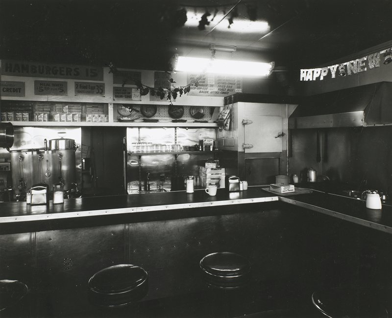 """corner of a lunch counter at a restaurant; menu signs at L; part of """"Happy New Year"""" sign at R"""