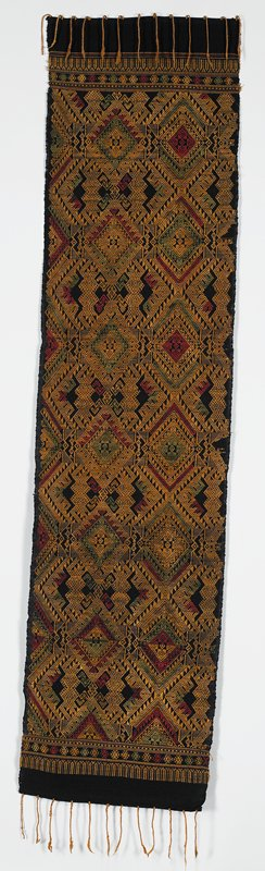 black ground; orange tassels; orange, red and olive green woven geometric design with flower and geometric borders