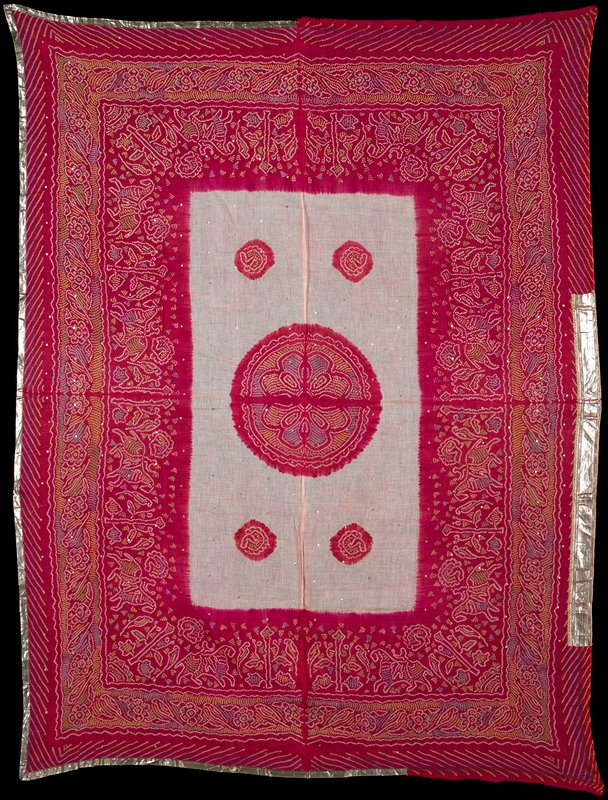 gauzy, tie-dyed fabric; red borders with birds, figures on horseback, trees and flowers in multicolored circles; central pink rectangle with one large red medallion and four small medallions; gold metallic and purple trim