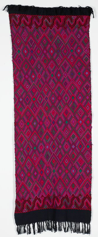dark blue ground; overall design of diamond and linear motifs in red, magenta, light purple, dark purple and green; blue fringe at short ends