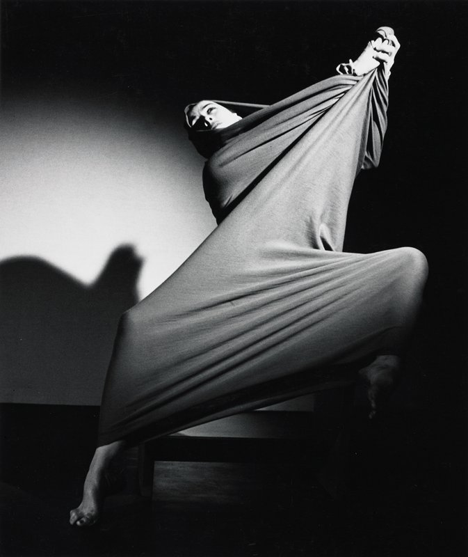 Martha Graham wrapped in a stretchy fabric; hood-like fold over head; fabric clutched in raised hands; shadow on wall behind