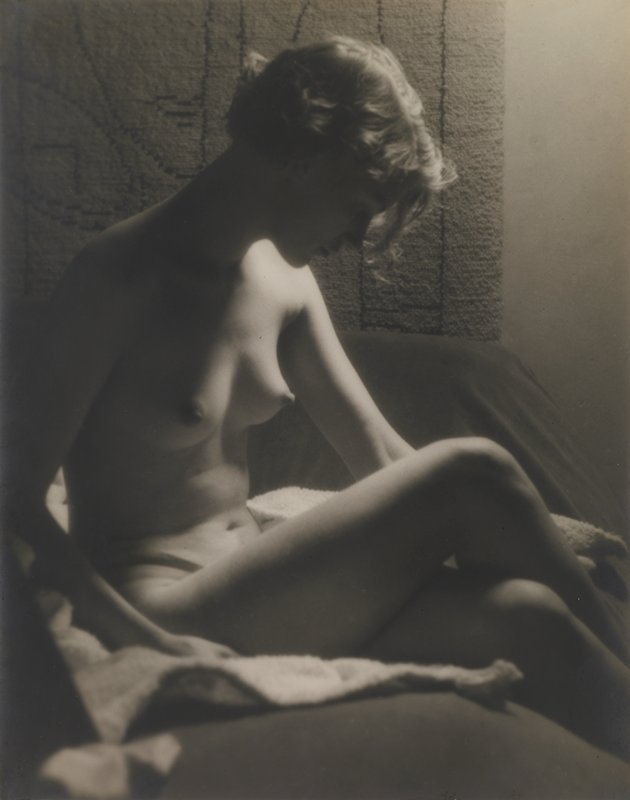 nude woman with light bobbed hair, seated, looking down; rug with linear design on wall behind woman