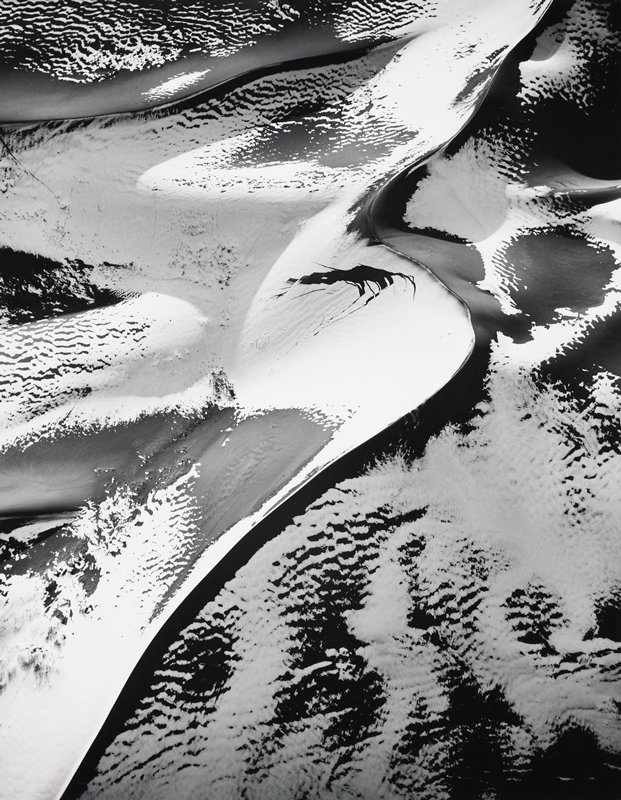 an aerial photograph of sand dunes partially covered with snow