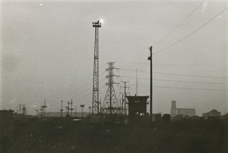 """tall tower with light on top; watchtower with """"UNION"""" sign; telephone and power poles and wires; grain elevator at right; grey sky"""