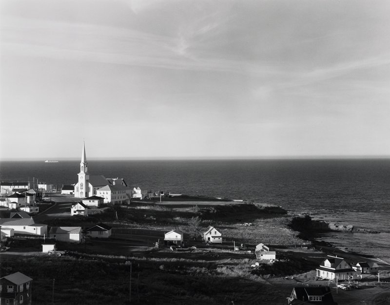 view of village, church at left center, freighter left at a distance