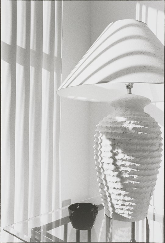 vase-shaped, rough-textured lamp base; cone-shape shade; on a glass table with black cup; sun through blinds cause shadows on lamp and wall