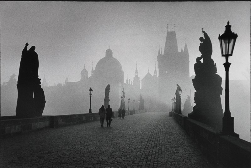 bridge over river; misty day; statues and lights left and right along bridge; cathedral visible through fog in background