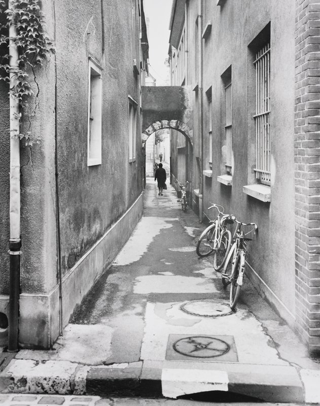 alley, three bicycles parked along right wall; female figure walking beneath arch, away from camera; male figure walking toward camera in distance