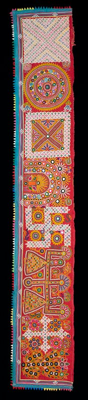 bright triangle fabric border; edged in turquoise with two-line chain stitches in white; linear appliqués in multicolors at edges; red fabric ground embroidered overall in bright colors with floral and small animal shapes, roundels and squares; embellished with mirrors; may be a pair with L2007.114.5