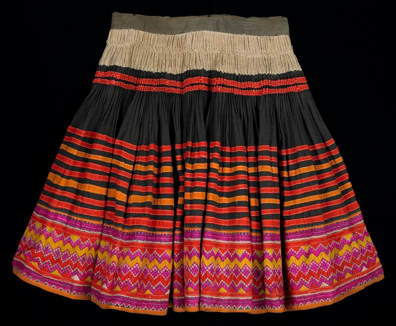 black with rough-woven tan and khaki fabric at top; rows of appliquéd orange and red bands; bottom hem decorated with red and yellow zigzags and pink and white cross stitch