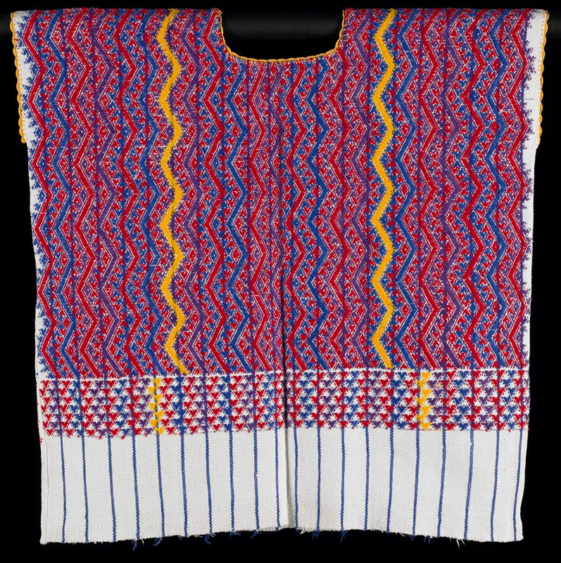 white with blue stripes; yellow scalloped crocheted trim at neckline and arm openings; woven at top with long vertical zigzags separated by zigzagging triangles in blue, purple, red and yellow; row of zigzagging triangles below