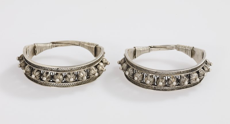 openwork bracelet with raised floral designs applied to openwork between upper and lower bands; center of each floral motif is an applied ball of metal; loops of very fine chain form petal like design on each motif; wire wrapped around bracelet at end of openwork