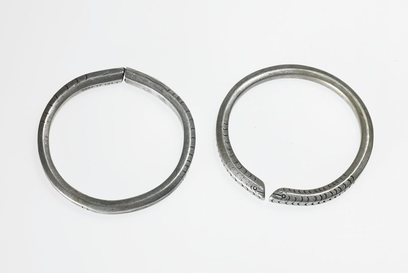 bracelet made from solid silver; snake or fish face etched on top, flat surface where ends meet and touch; scales etched throughout the bracelet; eye-like object etched in back center