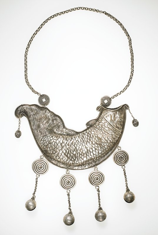 torque, large chain with a coin on each end; after the coin on each side, the chain attaches to a large hollow fish; the fish is open-mouthed; each end of the fish has small chains with tiny spheres dangling down; bottom of fish has four chains dangling from it; each chain has a large curlicue as well as a hollow bell; bells have a symbol etched into them