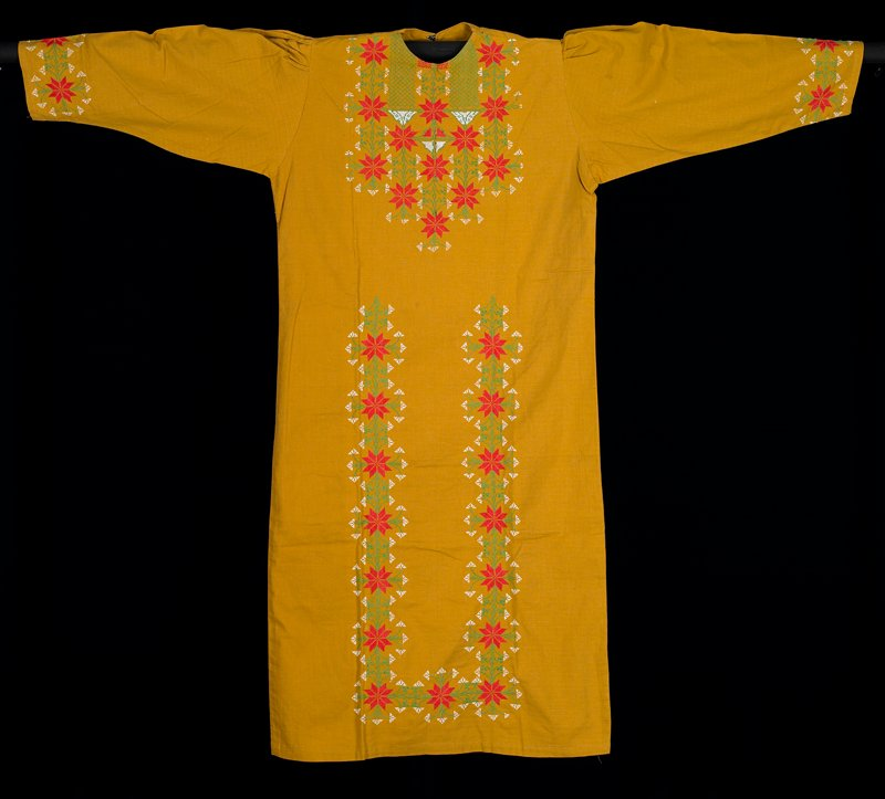 mustard yellow; long sleeves; rounded neck with hook at back of neck; cuffs, bib and front of skirt embroidered in cross stitches of white, green and red in star/ flower design Textiles-Surface Ornamentation-Needlework