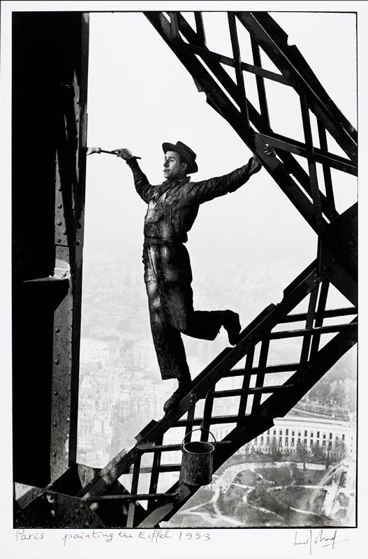 man wearing a hat and overalls, perched on a support on the Eiffel tower, painting; paint can below man's feet; city visible below