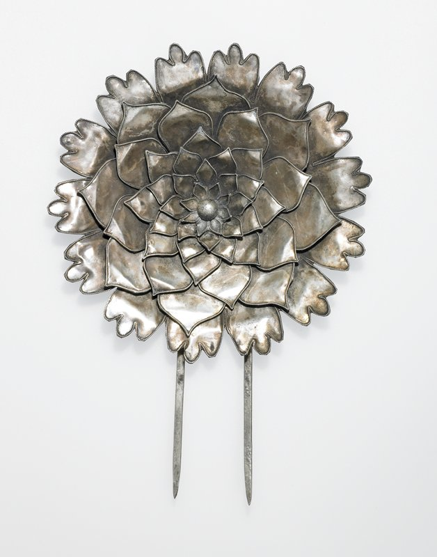 hair pin with flower-like motif at top; six or seven layers of petals with ball in center; two picks, one longer than the other