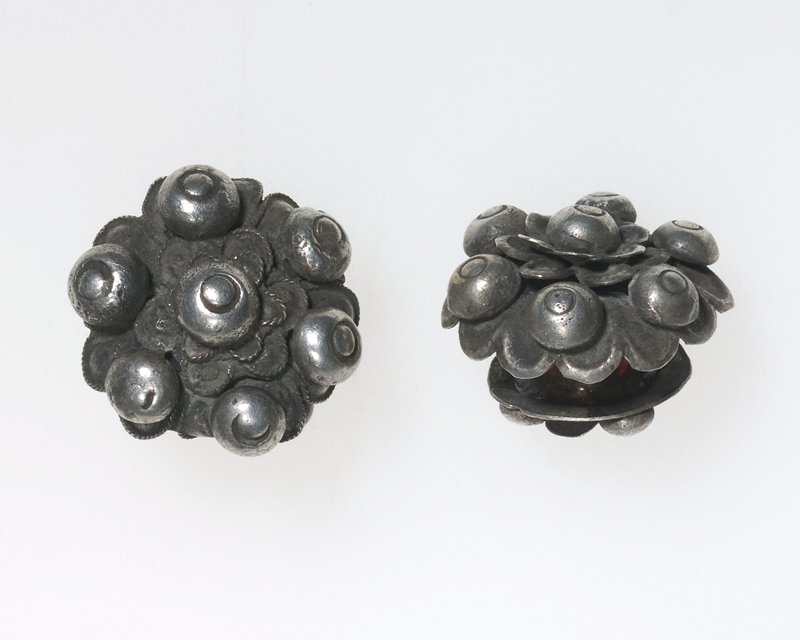 pair of ear plugs, large side of each ear plug has a flower decorated by six small spheres with circle shape indented in them; a sphere, with circle shape indented, rests in center on flat wire petals; back of plug has one sphere in center with four spheres surrounding it; back is smaller than the front