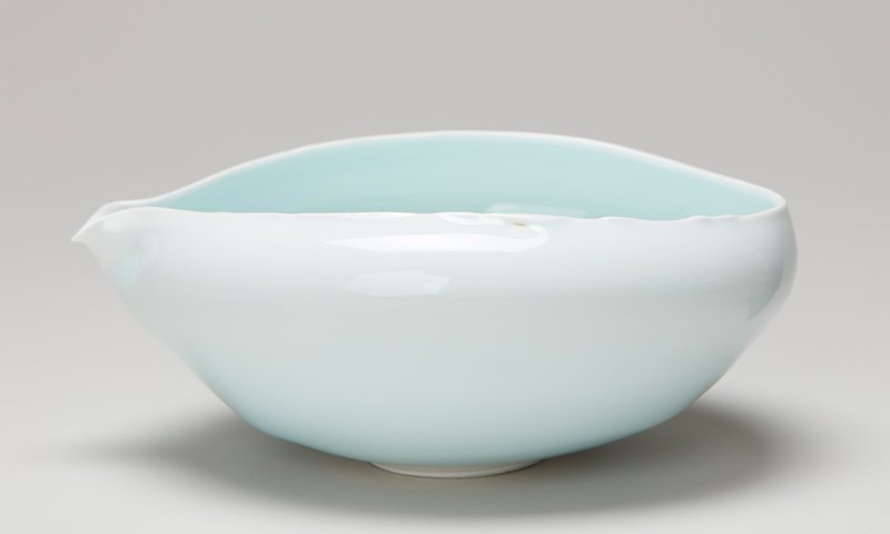 ovoid shape with round foot ring; sides flare inward at mouth rim with one side forming a small delicate spout; white clay with pale blue glaze
