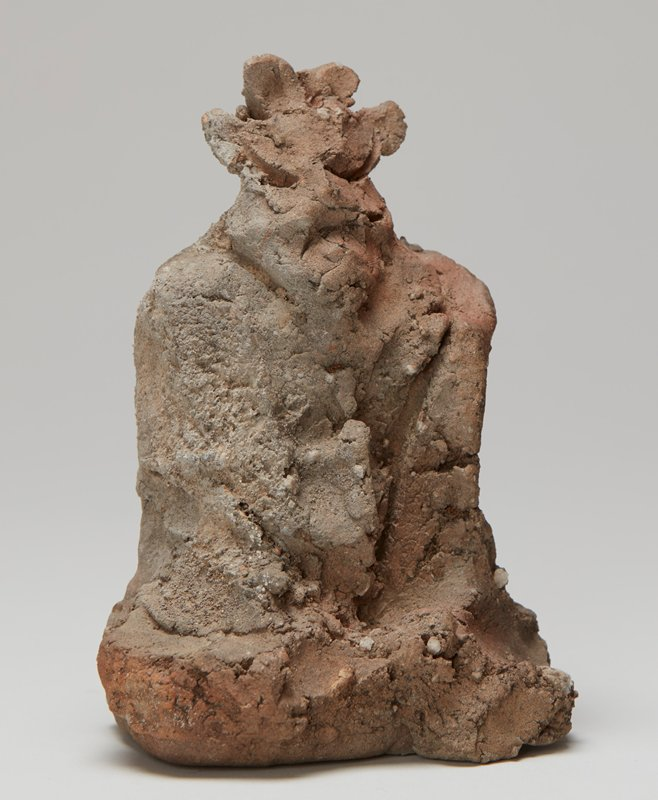 rather unarticulated rough clay; seated figure with four small protruding elements on top of head; large eyes--slashes--and frowning slash for mouth; red and dark grey