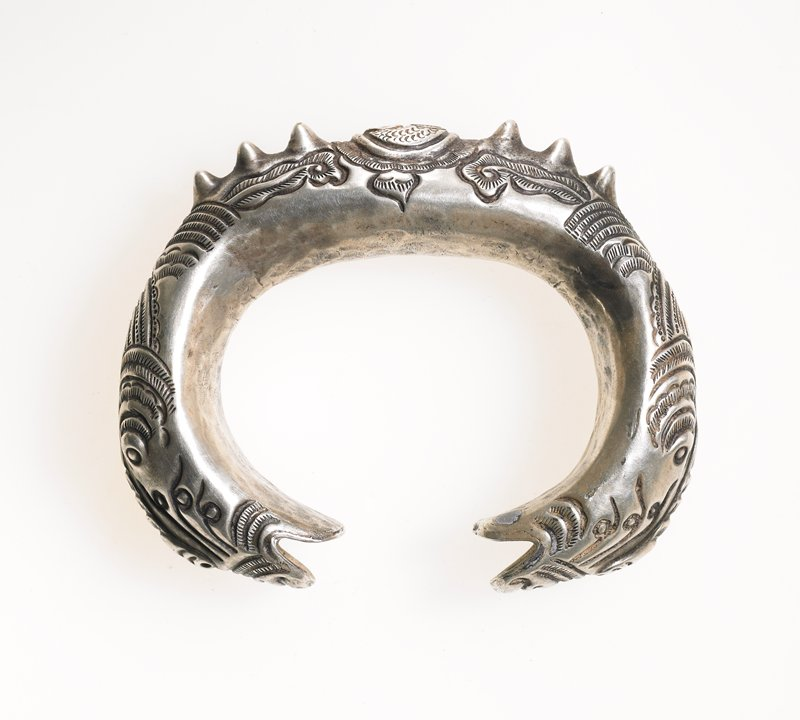 dragon bracelet; hollow; center motif nearly circular with two fish-like creatures in center surrounded by scalloped motif; three spikes on either side of center; foliate motif on sides below spikes; scale-like designs behind heads