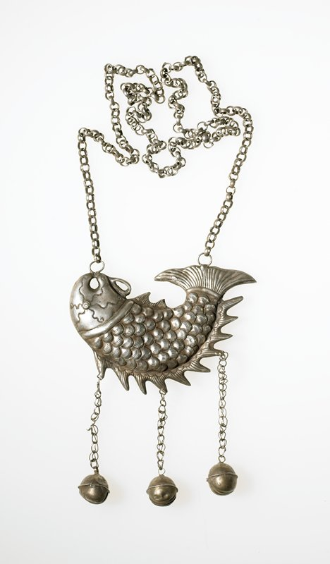 necklace with an extremely long chain; a curved fish dangles from the chain; three smaller chains dangle down from the fish from evenly-spaced spots on the fins; chains each have a bell-like sphere on the end