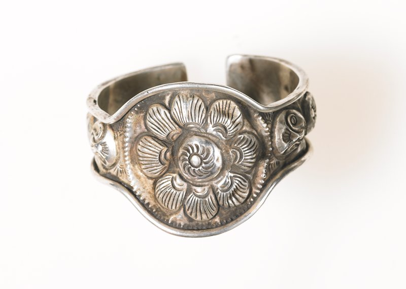 one of a pair of bracelets, center of bracelet is round with a flower medallion relief design; relief designs surround the medallion; four circular reliefs left-to-right from medallion on both sides: face, star, shell, face; thick smooth lip of silver runs around all edges, including the ends of the bracelet