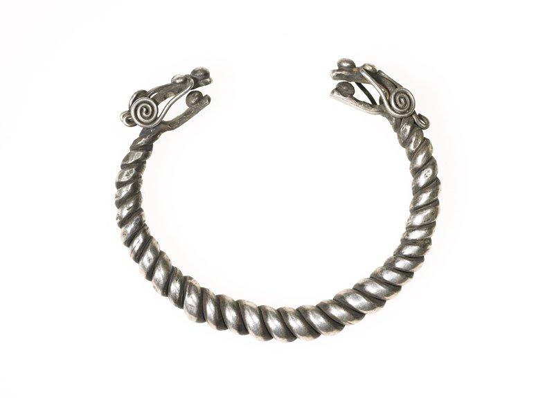 one of a pair of bracelets; bracelet made from loop of twisted wire; ends each have a dragon face; dragons have spheres between their jaws and large spheres on their noses; long thin wires make up the whiskers and end in loops and curlicues