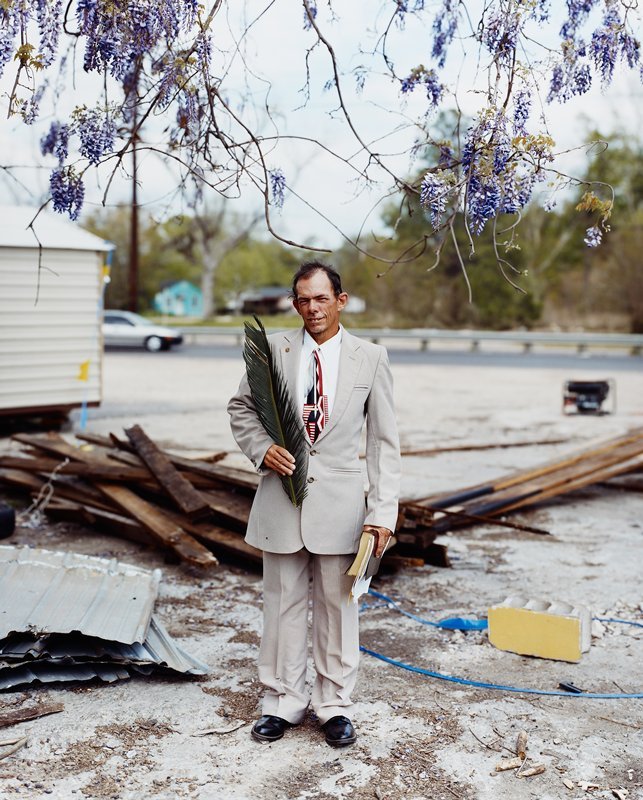 man wearing suit holding Bible in PL hand and palm branch in right hand; standing under blooming wisteria branch; construction debris
