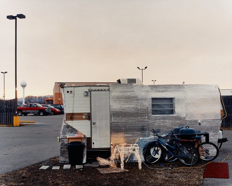 small trailer--silver--with two bikes, grill, lighted reindeer decoration in front; casino building in background