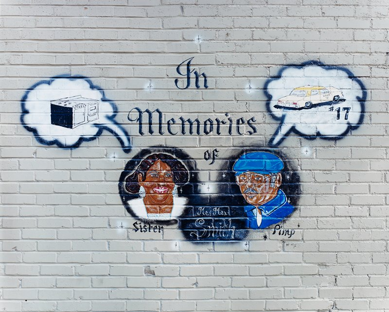 """In Memories of"" mural with portraits of a couple (""Mr. & Mrs. Smith""); ""Sister"" under woman, ""Pimp"" under man; thought balloon over woman's head with picture of a stove; thought balloon over man's head with picture of a taxi (""#17"")"