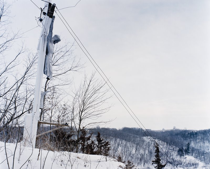 sculpture of crucified Jesus with missing legs--one leg attached below figure upside down--on power pole; snowy scene with trees