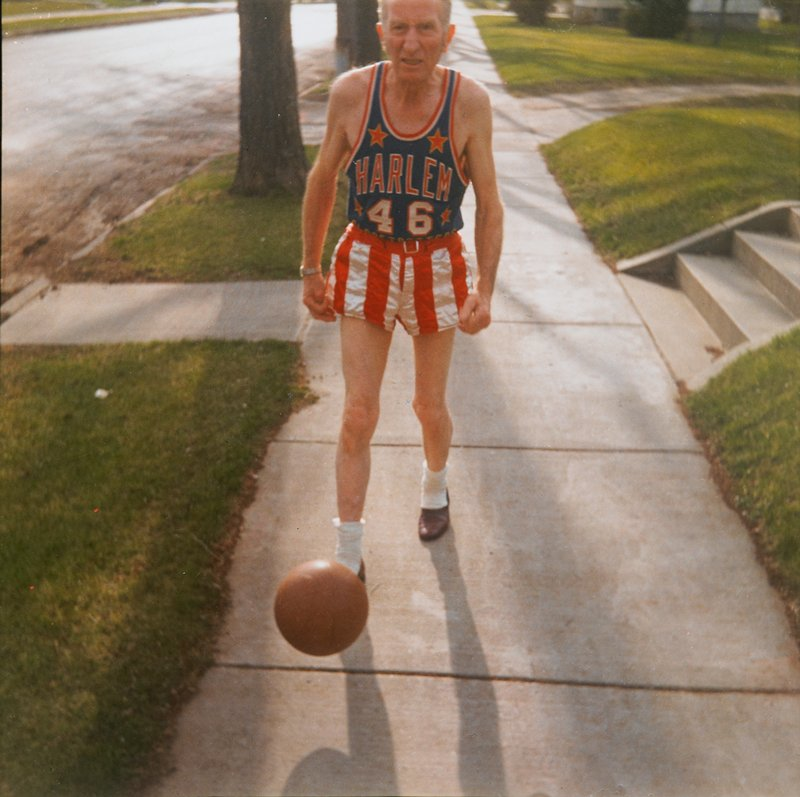 elderly man (Ray Muxter, Sr.), wearing a red, white and blue Harlem Globetrotters uniform on a city sidewalk, kicking a basketball; same image as 92.48.1,2