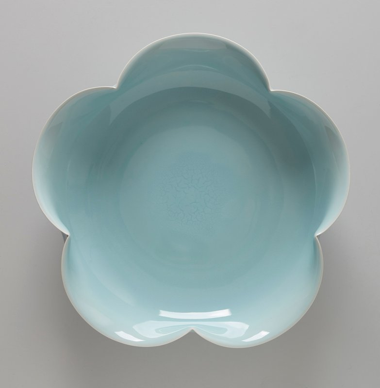 wide foot; rounded dish shape with five lobes at rim, forming flower-like shape; light blue