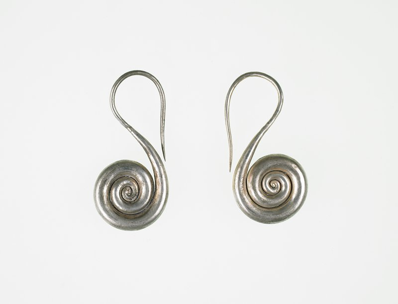 earrings are coils of thick, solid silver wire; wire thins to a point at end where it goes through the ear; earpiece end curves over to form a loop