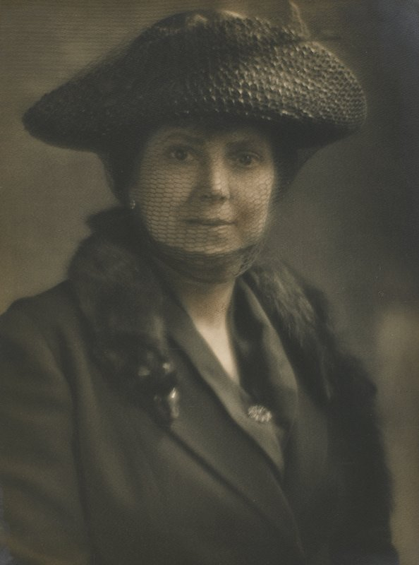 head and shoulders portrait of a woman wearing hat with veil which covers face and chin; fur neckpiece over jacket; pin on blouse