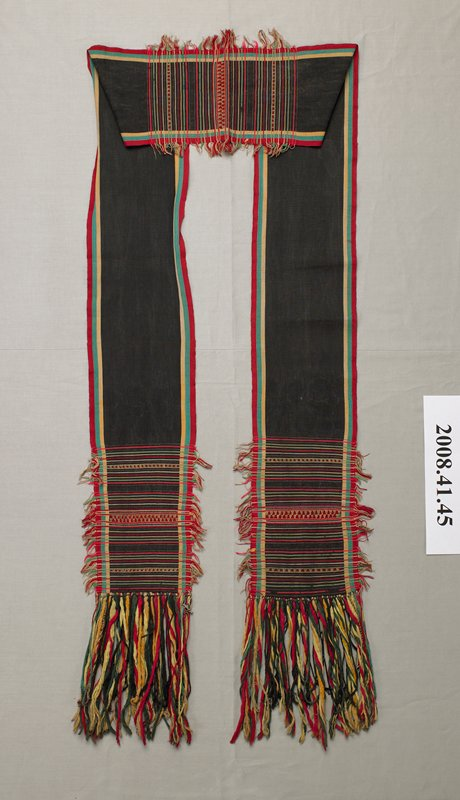 long black strip with green, yellow and red stripes on each long side; decorated at center and on each end with stitched stripes with fringe in green, pink, red, tan and yellow; long twisted fringe ends