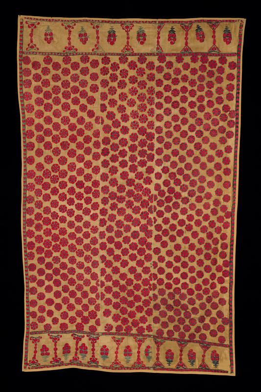 mustard yellow cotton fabric, attached to support fabric of the same color; overall embroidery of red and green floral roundels; chased red buds with green foliage at long sides; border at edges with floral clusters and decorative red and green organic designs