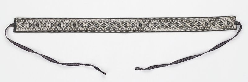 black fabric band embroidered on one side in white with repeating star and diamond motif; dark blue and white woven ties