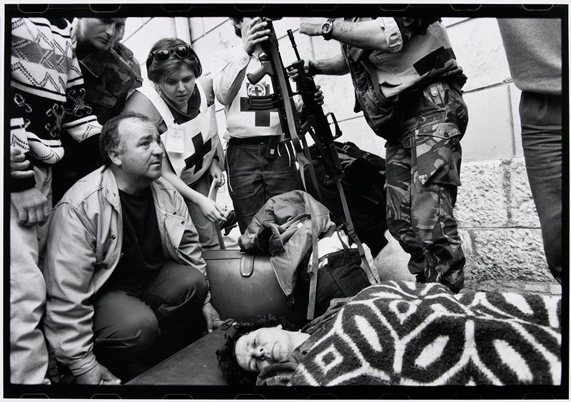 Red Cross and military personnel around a woman lying down