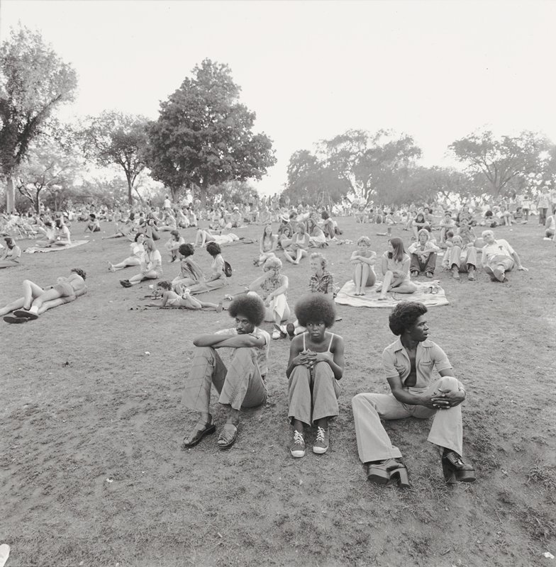 many groups of people seated on ground in park; three figures in foreground with big hair